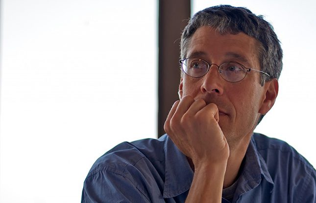 Portrait Image of Steven Nadler wearing a blue shirt and glasses with his hand on his chin in front of a bright window