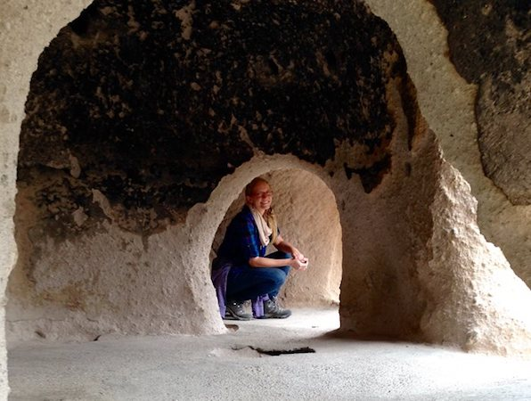 Picture of Katie Apsey wearing jeans and a blue shirt crouched in a cave