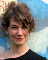 Portrait image of Amanda Jo Goldstein in front of a painted wall.