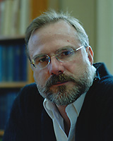 Portrait of Michael Bernard-Donals in front of book shelves wearing a black jacket and glasses