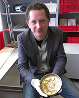 Portrait image of Richard Leson holding a medieval bowl in a museum collections area