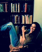 Portrait image of Amanda Rogers reclining in a chair in front of book shelves.