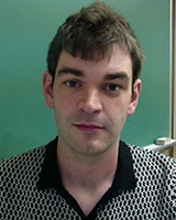 Portrait image of Darryl Wilkinson in front of green wall