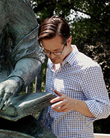 Image of Joshua Calhoun examining a bronze sculpture outdoors