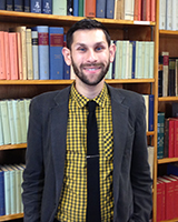 Portrait image of Theodore Martin in front of book shelves wearing a yellow and black checkered shirt, black tie, and grey jacket.