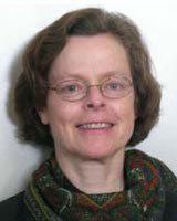 Portrait image of Julia Murray wearing thin glasses and a patterned scarf