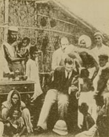 Sepia-toned image of a seated doctor in a suit attending to various Indian patients