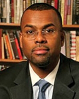 Portrait image of Eddie Glaude seated in front of book shelves wearing glasses, a black suit, and a blue tie