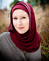 Portrait image of G. Willow Wilson outdoors in a field wearing a grey shirt and a maroon head scarf.