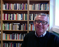 Portrait image of Simon Gaunt seated in front of bookshelves wearing glasses and a black sweater