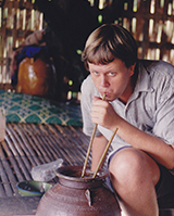 Field Image of Ian Baird drinking from a large ceramic container