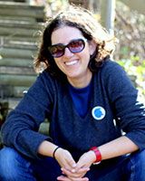 Portrait image of Ayelet Ben-Yishai seated outdoors wearing sunglasses, jeans, and a blue shirt