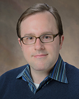 Portrait image of James Bromley wearing a dark blue shirt and glasses