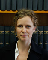 Portrait image of Julie Gibbings wearing a white shirt and black jacket standing in front of book shelves lined with blue books