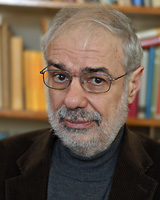 Portrait image of Leonard (Len Kaplan) in front of books