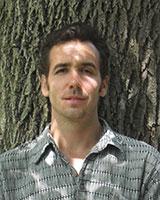 Portrait image of Micah Morton outdoors near a tree.