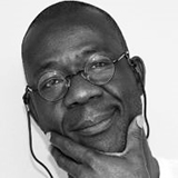 Black and White portrait image of Teju Olaniyan wearing glasses and a light shirt with his hand at his chin.