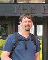 Portrait image of Stephen Pierce outdoors wearing a black backpack.