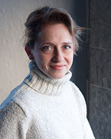 Image of Jennifer Ratner-Rosenhagen standing in front of a stone wall wearing a white sweater