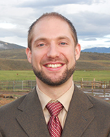 Portrait image of Scott Trudell standing outside wearing a brown suit and red striped tie