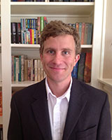 Portrait image of Brett Whalen in front of bookshelves