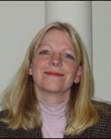 Portrait image of Louise Young wearing a pink turtle neck and checkered jacket