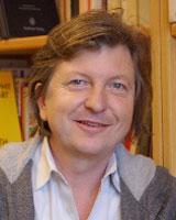 Portrait image of Niklaus Largier in front of bookshelves wearing a grey hooded sweatshirt