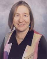 Portrait image of Susan Friedman with straight hair, long earrings, and a colorful shirt