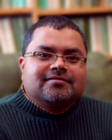 Portrait of Venkat Mani seated in a library wearing glasses and a ribbed sweater