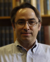 Portrait image of Mark Netzloff wearing a button-up light-colored shirt and glasses standing in front of bookshelves