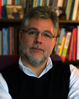 Portrait image of Russ Shafer-Landau in front of book shelves.