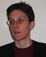 Portrait image of Claire Wendland in front of a white wall wearing a black shirt and glasses