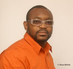 Portrait image of Jean-Pierre Bekolo wearing an orange shirt and clear glasses
