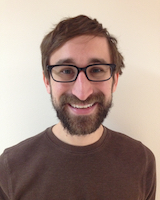 Portrait image of Andrew Zolides wearing a brown shirt and glasses standing in front of a white wall