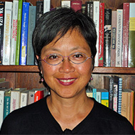 Portrait image of Christine Yano standing in front of book shelves wearing a black shirt and glasses