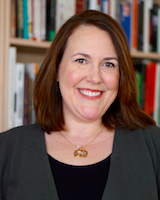 Portrait image of Jennifer Pruitt in front of book shelves.