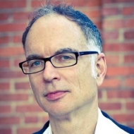 Portrait image of Ken Wissoker standing in front of a brick wall wearing a suit and dark-rimmed glasses