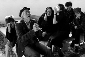 Black and white photograph by James Nachtwey of a family grieving and praying