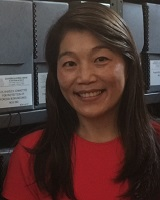 Portrait image of Cindy I-Fen Cheng wearing a red shirt standing in front of shelves of grey archival boxes