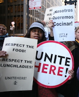 Image of a picket line with a woman holding various lunch-lady protest signs in English and Spanish