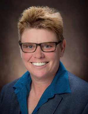 Portrait image of Madelyn Detloff wearing glasses and and blue shirt and grey jacket