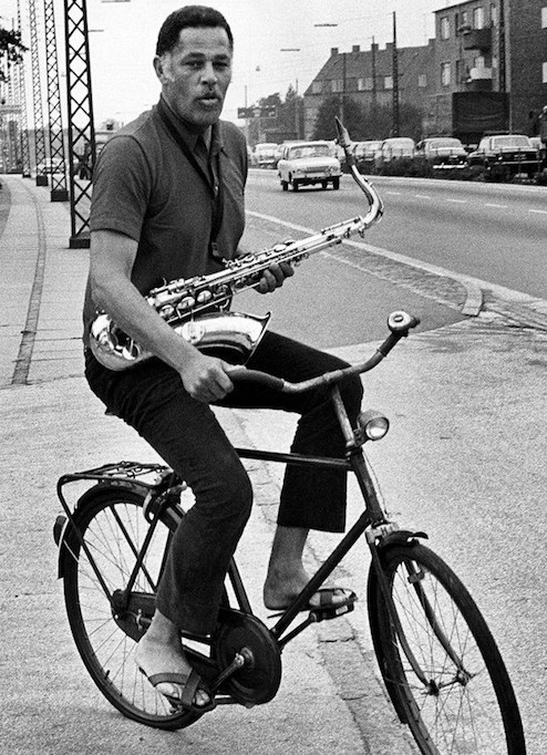 Image of Dexter Gordon on a bicycle carrying his saxaphone via a neck strap and one hand