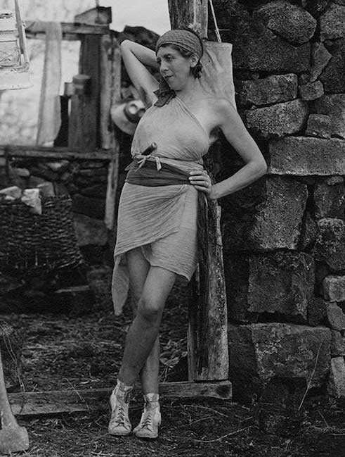 """The """"Baronessa,"""" a Viennese colonist, poses against a stone wall in a tattered costume for a film shot during the 1933 Hancock-Pacific expedition."""