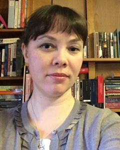 Portrait image of Sarah Crover wearing a grey shirt in front of book shelves