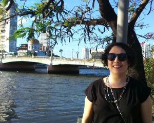 Portrait image of Falina Enriquez outdoors near a bridge wearing a black shirt and sunglasses