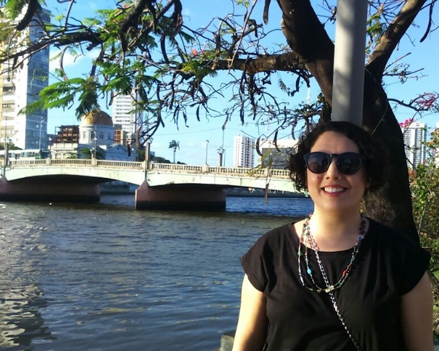 Portrait image of Falina Enriquez outdoors near a bridge wearing a black shirt and sunglasses