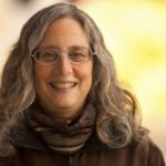 Portrait image of Lea Jacobs with shoulder-length grey hair in front of a blurred yellow background wearing a scarf, brown shirt, and clear glasses