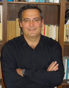 Portrait image of Paul-Alexis Mellet wearing a black shirt with arms crossed in front of a book shelf