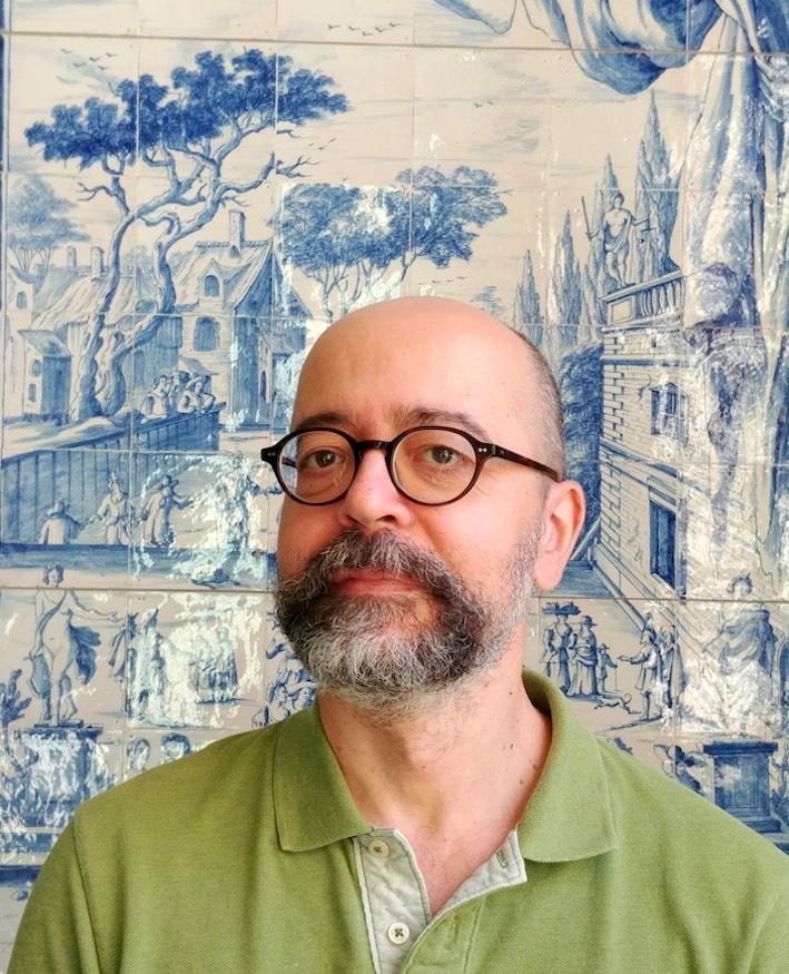 Portrait image of Giorgio Pini in front of a blue and white ceramic art piece