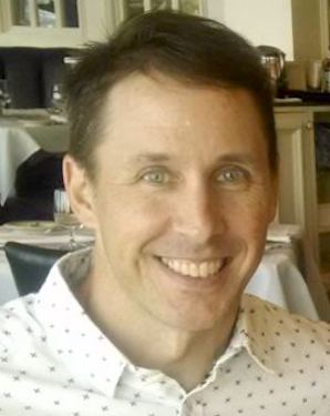 Portrait image of Edward Schmitt wearing a white shirt